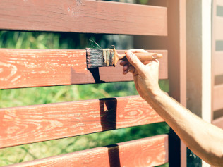 A painting contractor staining a fence in Lubbock, TX
